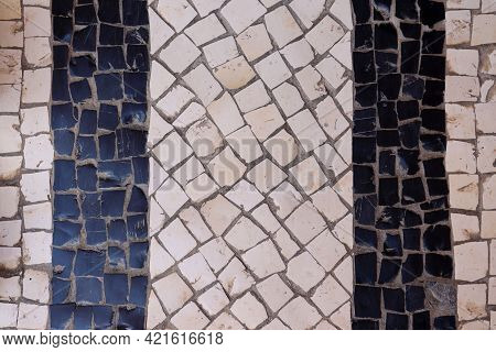 Sidewalk In Portugal. Handmade Mosaic In White And Black Stone. Traditional Cobblestone Pattern (cal