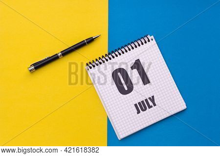 July 1st. Day 1 Of Month, Calendar Date. Notebook With A Spiral And Pen Lies On A Yellow-blue Backgr