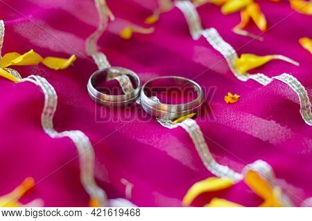 Two Platinum Engagement Or Wedding Rings Isolated On Pink Background. Symbol For Marriage, Love, Rel