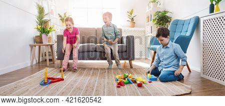 Playful Children Sitting In The Living Room On The Birthday Party. Concept Of The Human Relationship