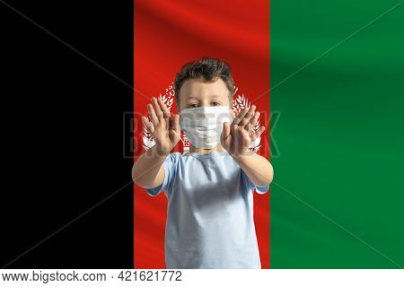 Little White Boy In A Protective Mask On The Background Of The Flag Of Afghanistan. Makes A Stop Sig