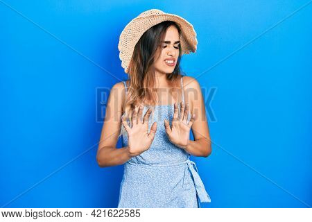 Young hispanic girl wearing summer hat disgusted expression, displeased and fearful doing disgust face because aversion reaction. with hands raised