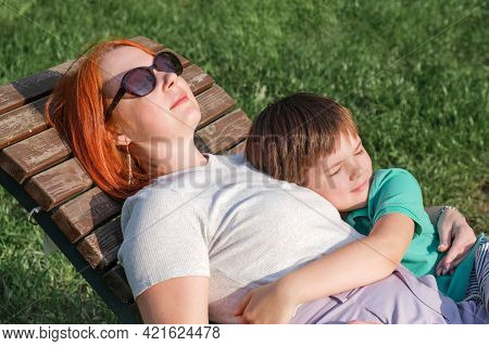 Young Woman With Red Hair And Boy Are Lie In Park On Wooden Deck Chair. Son Hugs His Mother Gently.