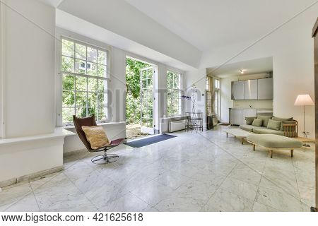Big Mansion Room With Tiled Floor Furnished With Settee And Armchair And Small Kitchen Cabinets In C