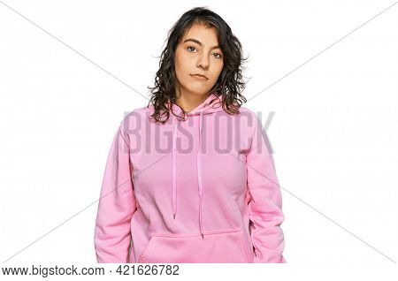 Young hispanic woman wearing casual sweatshirt looking sleepy and tired, exhausted for fatigue and hangover, lazy eyes in the morning.