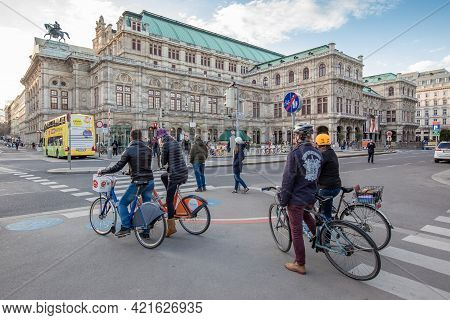 Vienna, Austria - 6 April 2015 - Cyclists Wait At The Crossroad Across From Vienna State Opera House