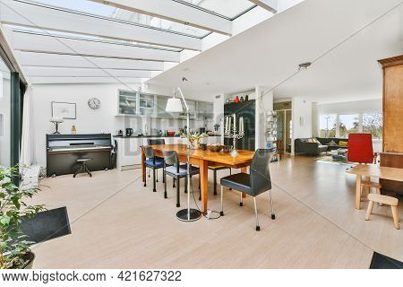 Spacious Mansion Kitchen Room With Glass Walls And Ceiling Above Wooden Dining Table In Daylight