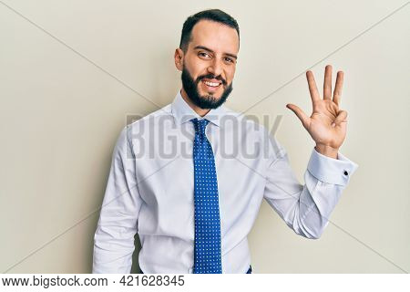 Young man with beard wearing business tie showing and pointing up with fingers number four while smiling confident and happy.