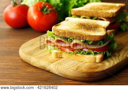 Sandwich With Ham, Green Lettuce And Tomato On A Wooden Brown Kitchen Board.