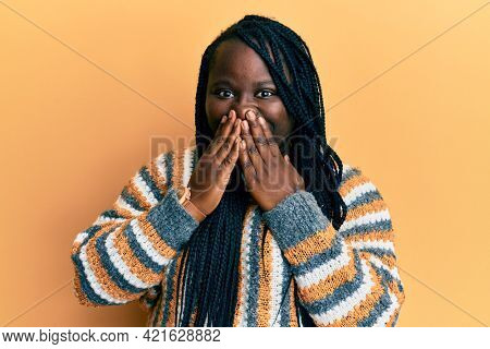 Young black woman with braids wearing casual winter sweater laughing and embarrassed giggle covering mouth with hands, gossip and scandal concept