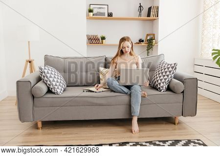 girl sitting on the couch works using a laptop and makes notes in a notebook.