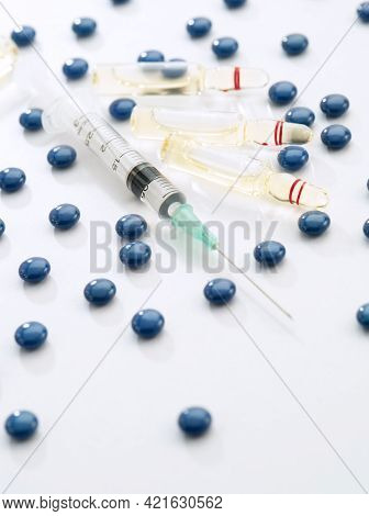 Close Up View Of The Ampule With Medicine, Pills And Syringe On White Back