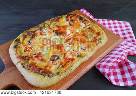 Mouthwatering Fresh Baked Homemade Pesto Veggie Pizza On A Wooden Breadboard