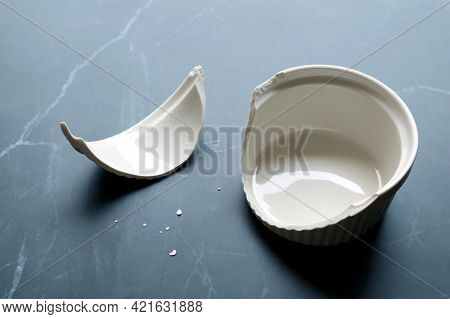 Broken White Ceramic Baking Bowl With Fragments On Black Marble Kitchen Counter Top