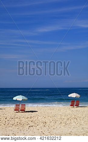Pairs Of Empty Red Beach Chairs With Parasols On The Sandy Beach Facing The Splashing Waves On Vivid