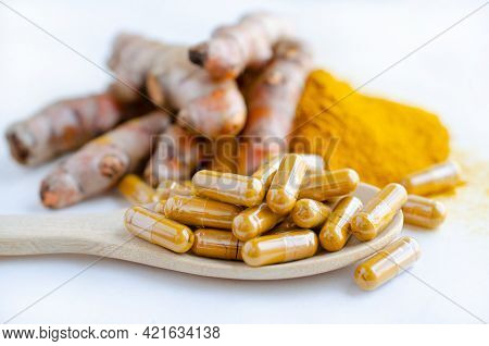 Closed Up Extract Pure Organic Turmeric Or Curcumin Powder In Capsule Over Blur Background Of Turmer