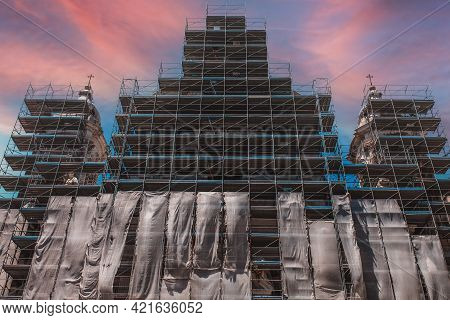 Restoration of the monument. Reconstruction and restoration of the old building. Metal scaffolding around a large and tall building at a construction site. An ancient building undergoing renovation covered with steel scaffolding. Restoration and maintenan