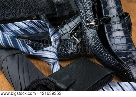 Close-up Of Men's Fashion Accessories. Umbrella And Tie, Shoes And Wallet On The Background Of A Lea