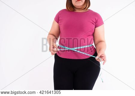 An Overweight Woman Measures Her Belly Fat On A White Background. Concept Of Healthy, Food For  Heal