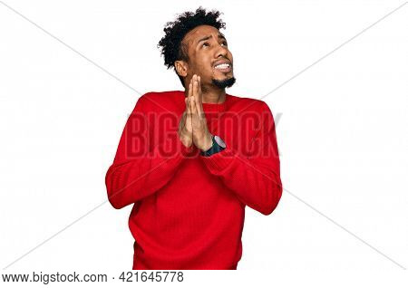 Young african american man with beard wearing casual winter sweater begging and praying with hands together with hope expression on face very emotional and worried. begging.