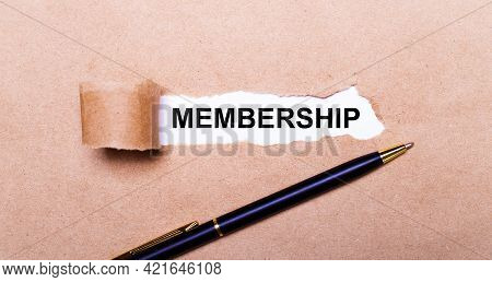 Torn Kraft Paper, White Background With The Text Membership. Nearby Is A Black Handle. View From Abo
