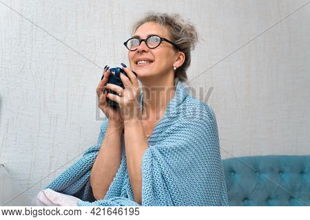 Happy Woman Drinking Coffee At Home. Smiling Lady Wrapped In A Warm Blanket And Enjoying A Drink. Ho