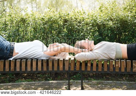 Two Happy Women Having A Rest On A Park Bench. Girl Tickling Her Girlfriend. Smiling Female Friends