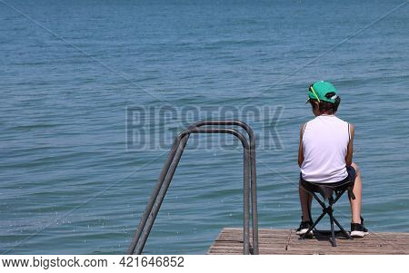 Lonely Child Sitting In The Chair On The Jetty