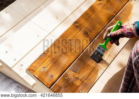 Painting Wooden Patio Deck With Protective Varnish.hand In Protective Gloves Holding Brush Painting