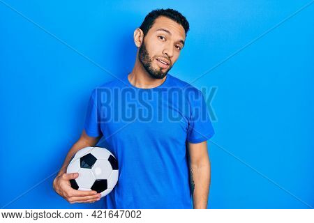 Hispanic man with beard holding soccer ball looking sleepy and tired, exhausted for fatigue and hangover, lazy eyes in the morning.
