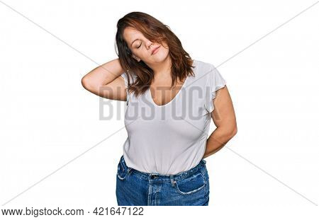 Young plus size woman wearing casual white t shirt suffering of neck ache injury, touching neck with hand, muscular pain