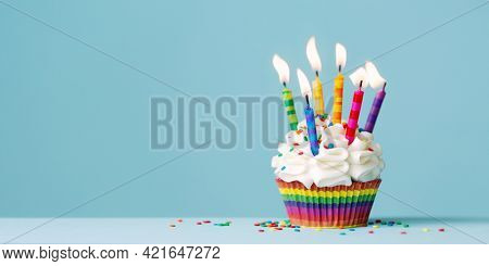 Birthday cupcake with lots of colorful birthday candles against a blue background with copy space to side