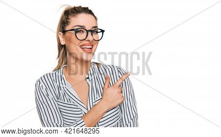 Young caucasian woman wearing business shirt and glasses cheerful with a smile of face pointing with hand and finger up to the side with happy and natural expression on face