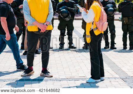 Legal Civil Observers In Yellow Jackets Stands On The City's Street Near Special Police Officers. Pr