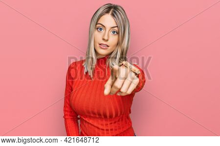 Beautiful blonde woman wearing casual clothes pointing displeased and frustrated to the camera, angry and furious with you