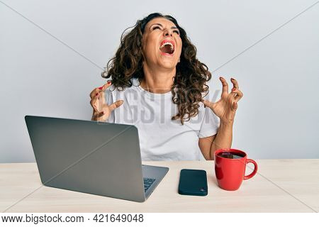 Beautiful middle age woman working at the office using computer laptop crazy and mad shouting and yelling with aggressive expression and arms raised. frustration concept.