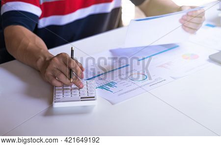 Businessman Using Calculator And Holding Paperwork, Business Profits Document. Financial And Tax Sys