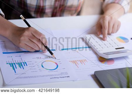 Businesswoman Uses Pen Pointing Graph Analyze And Calculate Data Statistic, Trade, Business Profits.