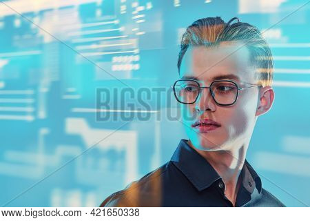 Business concept. Portrait of a handsome young man in elegant glasses on a blue background with digital holograms. Stock exchange.