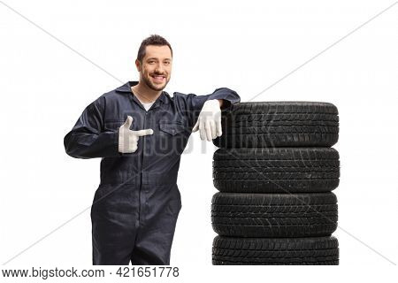 Auto mechanic leaning on a pile of tires and pointing isolated on white background
