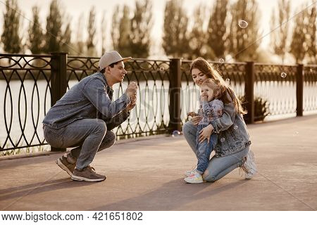 Stylish Family Dressed In Denim Clothes Walks Near The River And Has Fun Blowing Bubbles. Young Pare