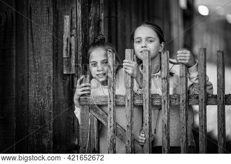 Two girls sisters or girlfriends in the village. Black and white photo.