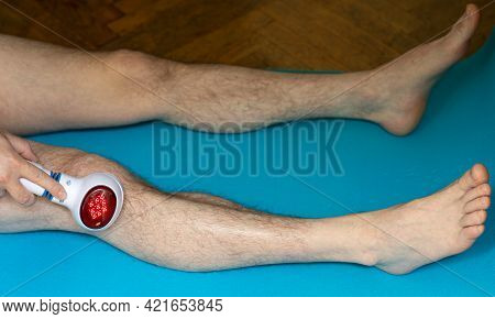 The Man Massages His Knee With An Electric Massager With A Red Light Of Heat