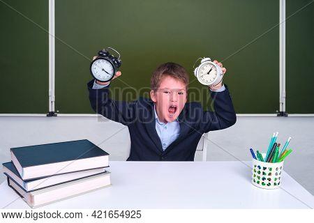 Funny Junior Boy With Alarm Clocks In The School Class. Schoolboy Screams At His Desk At The Blackbo