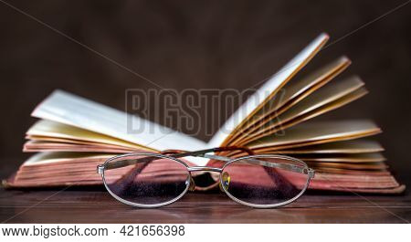 Story Book, Storytelling Concept, Old Book And Eyeglasses On A Wooden Background. Web Banner With Co