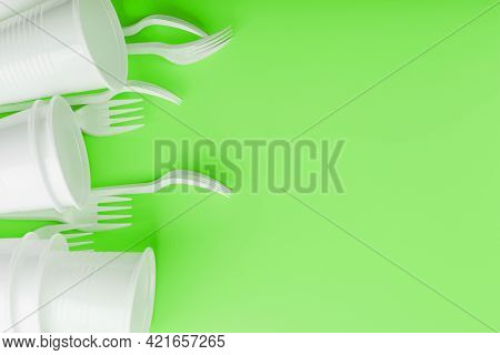 Disposable Plastic Tableware On A Green Background With Free Space.
