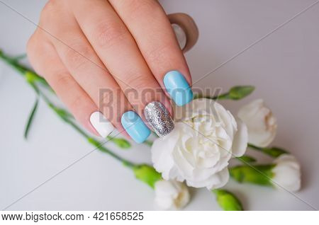 A Well-groomed Female Hand On A Background Of Carnation Flowers, A Manicure With Blue And White Gel