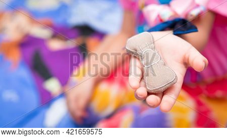 Child Playing Places Things On Her Arms And Hands So That They Don't Land On The Ground. Playing Wit