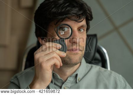 Man See Through Magnifying Glass. Male Taking A Magnifying Glass And Looking Through It