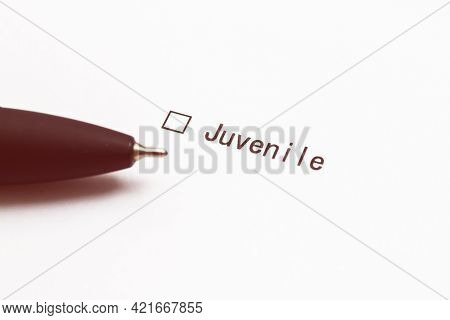 Pen And The Inscription Juvenile With A Check Mark On White Paper. Questionnaire.